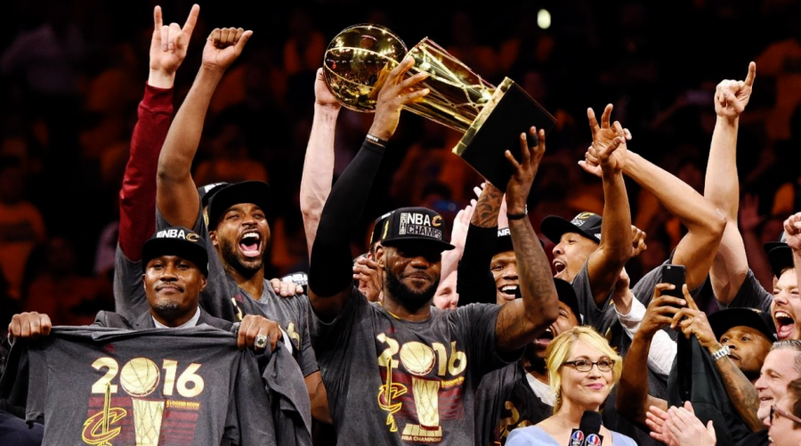 Lebron James lifting the Larry OBrien Trophy as he and the Cleveland Cavaliers celebrate, shortly after winning the 2016 NBA Finals against Stephen Curry and the Golden State Warriors.