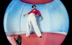 The album cover portrays Styles' through a fisheye lens. The pointing of the hands draws attention towards the fine line between masculinity and femininity represented by the pink and blue colors.